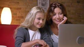 Closeupfors av den unga modern och hennes lilla nätta dotter som tillsammans använder bärbara datorn och talar med spänning på stock video