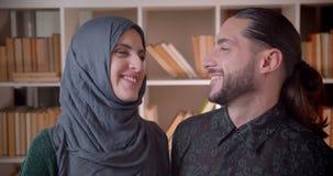 Closeupfors av den unga muslim affärskvinnan och affärsmannen som ser raka på kameran och glatt inomhus ler in arkivfilmer