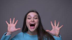Closeupfors av den unga nätta brunettkvinnlign som vänder runt om att le lyckligt och att skrika med glädje som ser kameran arkivfilmer