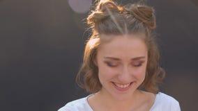 Closeupfors av den unga nätta caucasian kvinnlign med hårbullar som ler se lyckligt kameran med solsken och arkivfilmer