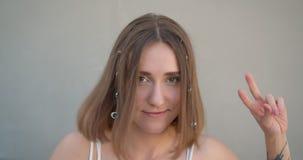 Closeupfors av den unga nätta caucasian kvinnlign med hårcirklar och att blänka retro se för makeupdans lyckligt stock video