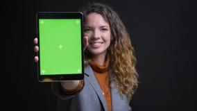Closeupfors av den unga nätta caucasian kvinnlign som använder minnestavlan och visar den gröna chromaskärmen till att le för kam fotografering för bildbyråer