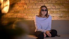 Closeupfors av den unga nätta caucasian kvinnlign som håller ögonen på en film för fasa 3D i exponeringsglas på TV:N och får förs stock video