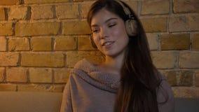 Closeupfors av den unga nätta caucasianen som hänsynsfullt lyssnar till musik i hörlurar i begrundande i en slags tvåsittssoffa royaltyfria foton