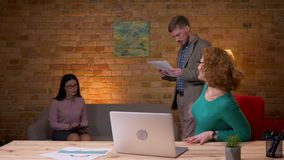 Closeupfors av den vuxna affärskvinnan som använder bärbara datorn som är spännande och inomhus firar med två kvinnliga kollegor stock video