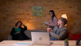 Closeupfors av den vuxna affärsmannen som skriver på bärbara datorn som är spännande och inomhus firar med två kvinnliga kollegor arkivfilmer