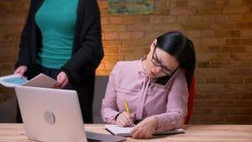 Closeupfors av den vuxna asiatiska affärskvinnan som skriver på bärbara datorn som har en konversation på telefonen och tar anmär arkivfilmer
