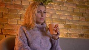 Closeupfors av den vuxna caucasian blonda kvinnlign som håller ögonen på en TVkomedishow rymma en kopp av varmt te, medan sitta p arkivfilmer