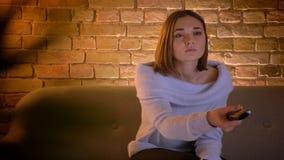 Closeupfors av hållande ögonen på TV för ung härlig caucasian kvinnlig med uppmärksamt ansiktsuttryck arkivfilmer