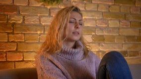 Closeupfors av hållande ögonen på TV för vuxen caucasian blond kvinnlig som är berörd och melankolisk, medan sitta på couh stock video