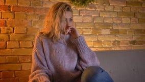 Closeupfors av hållande ögonen på TV för vuxen caucasian blond kvinnlig som trycks på, och den ledsna gråt, medan sitta på soffan arkivfilmer