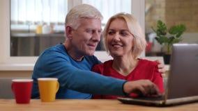 Closeupfors av höga lyckliga par genom att använda bärbara datorn på skrivbordet med koppar med te som lyckligt inomhus ler i en  stock video
