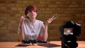 Closeupfors av kvinnlig video levande vloggertryckning för ung attraktiv hipster och annonsering av makeup, medan tala på arkivbilder