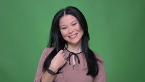 Closeupfors av unga attraktiva asiatiska kvinnlign som framme skrattar och den är glad av på kameran stock video