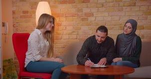 Closeupfors av unga lyckliga muslim par som diskuterar med en realter en ny lägenhet och undertecknar le för avtal arkivfilmer