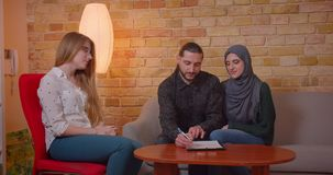 Closeupfors av unga lyckliga muslim par som diskuterar med en realter en ny l?genhet som ler glatt att sitta p? lager videofilmer