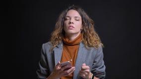 Closeupfors av ungt attraktivt caucasian kvinnligt smsa på telefonen och som framme irriteras av kameran med royaltyfri fotografi
