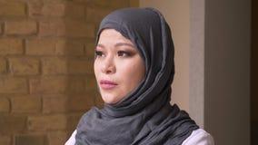 Closeupfors av vuxen muslim kvinnlig anställd i hijab som inomhus ser kameran i begrundande på arbetsplatsen stock video