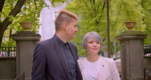 Closeupforsen av unga härliga hipsterpar som talar glatt att vara lycklig i, parkerar utomhus utomhus stock video