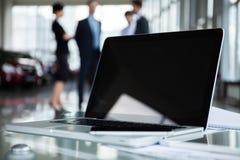 Closeupfoto av bärbar datordatoren med öppet överkant- och affärsfolk i bakgrund royaltyfria foton