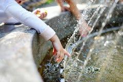 Closeupfoto av barntvagninghänder i en springbrunn Arkivbild