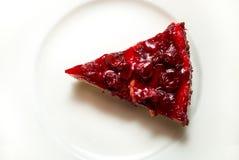Closeupfoto av den läckra körsbärsröda ostkakaskivan på den vita maträtten Royaltyfri Foto