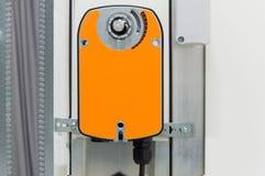 Closeupfoto av den orange stötdämparutlösaren som installeras på den industriella ventilationsenhetskroppen, främre sikt Arkivbilder