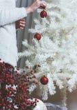 Closeupfoto av den unga kvinnan som dekorerar den vita julgranen på Arkivfoto