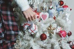 Closeupfoto av den unga kvinnan som dekorerar den vita julgranen på Royaltyfria Bilder