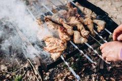 Closeupfoto av grillfestgallret med fegt k?tt p? utomhus- i sommartiden Man som lagar mat mat i natur arkivfoton