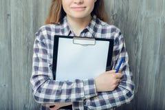 Closeupfoto av kvinnan som isoleras på grå träbakgrundsholdin arkivfoton