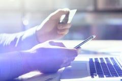 Closeupfotoaffärsman som arbetar med den generiska designsmartphonen Online-betalningcreditcard, händer tangentbord, bärbar dator Royaltyfria Foton