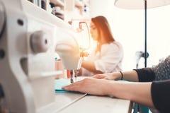 Closeupfotoet av ` s för den unga kvinnan räcker sömmerskasammanträde och syr på symaskinen i idérik märkes- studio Arkivfoto