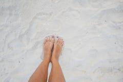 Closeupfotoet lägger benen på ryggen den avslappnande sandstranden för unga flickan Högt detaljerad bildbakgrund Horisontal föres Royaltyfri Foto