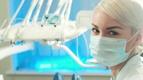 Closeupframsida av tandläkaren för ung kvinna i maskering på henne i tand- kontor stock video