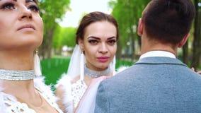 Closeupframsidor av ungdomar, i att gifta sig kl?der, st?r posera fortfarande f?r kamera lager videofilmer