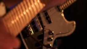 Closeupgitarrist Touches Strings på Finger-bräde i nattstång arkivfilmer