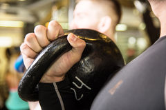 Closeupgungakettlebell som utbildar två unga män i idrottshallen Royaltyfria Bilder