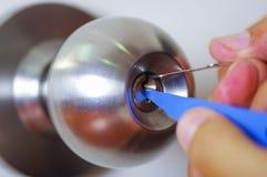 Closeuphänder av låssmeden som använder hackahjälpmedel för att öppna den låsta dörren royaltyfria bilder