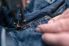Closeuphänder av skräddaremannen som arbetar på den gamla symaskinen textilen för jeanstorkduketyg shoppar in och att anpassa, sl royaltyfri fotografi