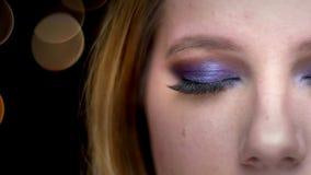 Closeuphalva-framsida fors av den unga härliga kvinnliga framsidan med ögon som ser kameran med bokehljus på bakgrunden arkivfilmer