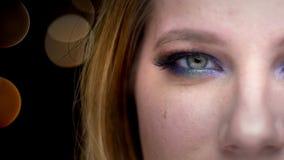 Closeuphalva-framsida fors av den unga härliga kvinnliga framsidan med ögon som ser kameran som ler med bokehljus på arkivfilmer