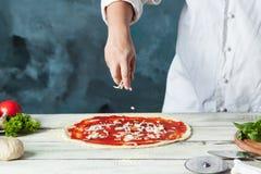 Closeuphand av kockbagaren i vit enhetlig danandepizza på kök Arkivbilder