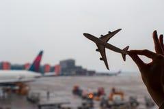 Closeuphand som rymmer en flygplanmodell på flygplatsen Royaltyfria Foton