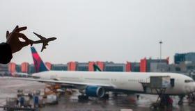 Closeuphand som rymmer en flygplanmodell på flygplatsen Royaltyfri Fotografi