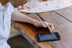 Closeuphanden av asiat man genom att använda en mobiltelefon fotografering för bildbyråer