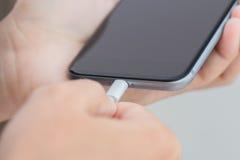 Closeuphanden som använder usb-kabel, förbinder till telefonen arkivbild