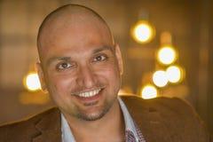 Closeupheadshotstående, lycklig stilig indisk affärsman och att le, säkert och vänligt inomhus arkivbild