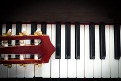 Closeuphuvud av gitarren på pianotangentbordet Arkivbild