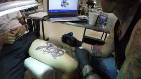 Closeupkonstnär Draws Funny Tattoo på Guy Leg Using Tool lager videofilmer